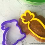 orange slime and Easter cookie cutters on white counter